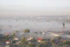 Ajardine com árvores e construções na névoa Imagens de Stock Royalty Free