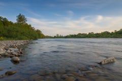Ajardine com árvores, pedras, céu azul com as nuvens inchado a do branco Foto de Stock Royalty Free