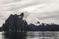 Ajardine com as árvores das montanhas do fundo e a névoa e um lago na parte dianteira, nivelando após o dia chuvoso pesado Condiç Imagens de Stock