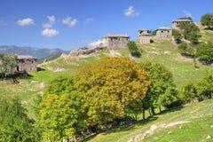 Ajardine com as casas de pedra velhas na montanha Fotografia de Stock