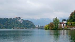 Ajardine com as casas e o castelo sangrado que cercam o lago sangrado em Eslovênia Fotos de Stock Royalty Free