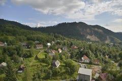 Ajardine com as casas em Rosia Montana, Romênia, Europa Imagens de Stock