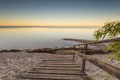 Ajardine com as escadas de madeira que conduzem ao mar Imagem de Stock