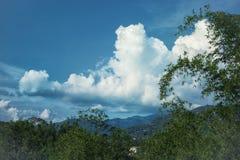 Ajardine com as montanhas cobertas com a floresta e o céu clody Imagem de Stock Royalty Free