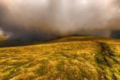 Ajardine com as montanhas de Fagaras em Romênia e as nuvens entre t Imagem de Stock