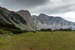Ajardine com as nuvens escuras sobre o pico de Sinanitsa, montanha de Pirin Imagem de Stock