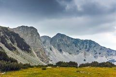 Ajardine com as nuvens escuras sobre o pico de Sinanitsa, montanha de Pirin Fotografia de Stock