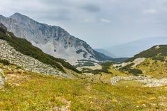 Ajardine com as nuvens escuras sobre o pico de Sinanitsa, montanha de Pirin Imagens de Stock