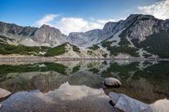 Ajardine com as nuvens escuras sobre o pico e o reflectionin de Sinanitsa o lago, montanha de Pirin Fotos de Stock