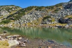 Ajardine com as pedras na água no lago pequeno, montanha de Rila Imagens de Stock