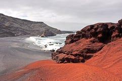 Ajardine com as rochas vermelhas da lava na ilha espanhola Lanzarote Foto de Stock