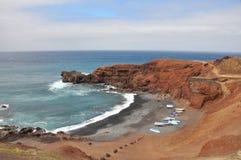 Ajardine com as rochas vermelhas da lava na praia da ilha espanhola Lanzarote Fotos de Stock