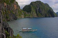 Ajardine com barco do filippino, rochas e a baía azul EL Nido, ilha de Palawan, Filipinas Fotografia de Stock Royalty Free