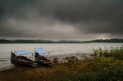 Ajardine com barco e mar sob a chuva e o céu nebuloso no Fotos de Stock Royalty Free