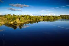 Ajardine com céu azul e superfície lisa do lago Fotografia de Stock Royalty Free