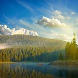 Ajardine com céu azul, montanhas, lago e barco Foto de Stock Royalty Free