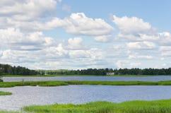 Ajardine com céu azul, nuvens, floresta e lago Foto de Stock Royalty Free