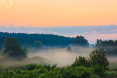 Ajardine com céu do nascer do sol, casas na névoa bonita na manhã Imagem de Stock