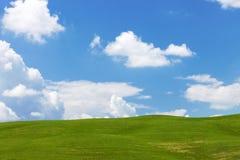 Ajardine com céu, nuvens, montes e grama Imagem de Stock