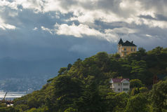 Ajardine com céu pre-tormentoso e casas no monte Foto de Stock Royalty Free