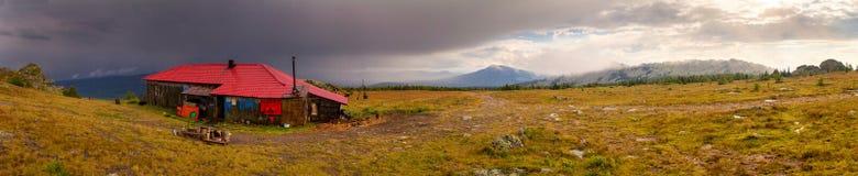 Ajardine com céu tormentoso e abrigue nas montanhas Fotos de Stock