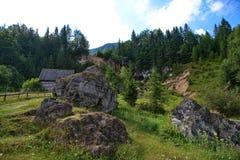 Ajardine com cachoeira, as rochas e a casa de campo distantes Fotografia de Stock Royalty Free