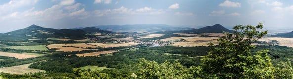 Ajardine com campo, vilas, os montes isolados, a cordilheira no fundo e o céu azul com nuvens Imagens de Stock