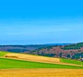 ajardine com campos e uma vila com montes Foto de Stock
