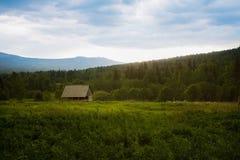 Ajardine com a casa contra a madeira das montanhas e do s Foto de Stock Royalty Free