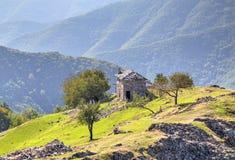 Ajardine com a casa de pedra velha na montanha Fotos de Stock