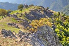 Ajardine com a casa de pedra velha na montanha Imagem de Stock Royalty Free