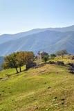 Ajardine com a casa de pedra velha na montanha Foto de Stock Royalty Free
