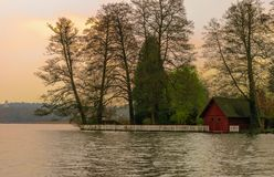 Ajardine com casa e as árvores vermelhas perto de um lago em Alemanha imagem de stock