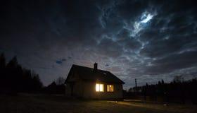 Ajardine com a casa na noite sob o céu nebuloso Fotos de Stock