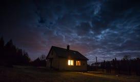 Ajardine com a casa na noite sob o céu nebuloso Fotografia de Stock