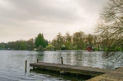 Ajardine com casa vermelha perto de um lago em Alemanha imagem de stock