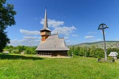 Ajardine com crucifixo e a igreja de madeira romena com plano poligonal Fotos de Stock Royalty Free