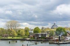 Ajardine com diversas casas holandesas e rio sob o céu nebuloso Fotos de Stock Royalty Free
