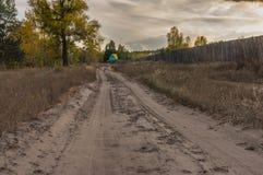 Ajardine com a estrada arenosa que conduz à casa colorida verde-amarela pequena Fotos de Stock Royalty Free