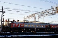 Ajardine com a estrada de ferro com trens, lote das vigas de aço no por do sol Fotografia de Stock Royalty Free