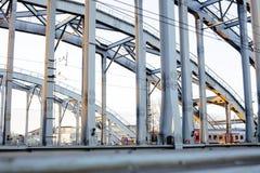 Ajardine com a estrada de ferro com trens, lote das vigas de aço no por do sol Imagens de Stock