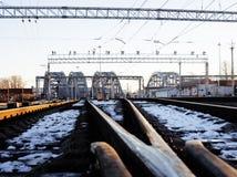 Ajardine com a estrada de ferro com trens, lote das vigas de aço no por do sol Fotografia de Stock