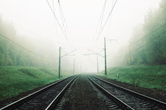 Ajardine com a estrada de ferro na floresta na névoa fotos de stock royalty free