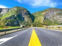Ajardine com a estrada do campo no dia ensolarado em Noruega Fotografia de Stock