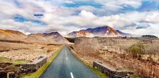 Ajardine com estrada e montanhas em um dia nebuloso Imagens de Stock Royalty Free