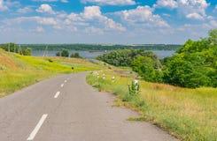 Ajardine com estrada e o prado rurais na borda da estrada perto do rio de Dnepr, Ucrânia Imagem de Stock Royalty Free