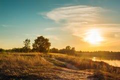 Ajardine com estrada em um campo perto de um rio Por do sol Imagem de Stock