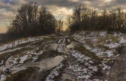 Ajardine com a estrada extremamente suja que conduz à vila ucraniana pequena Shpilivka no oblast de Sumskaya, Ucrânia Imagem de Stock