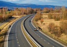 Ajardine com estrada, os carros do passeio três da estrada Fotos de Stock Royalty Free