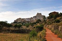 Ajardine com a estrada rural com castelo e cidade Foto de Stock